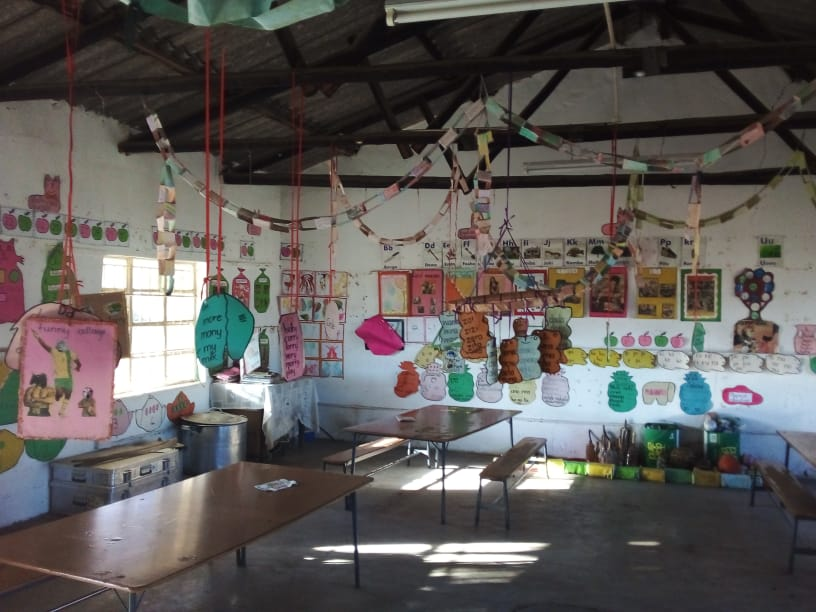 Picture from the inside of a classroom at Muda School, showing tables and colourful artwork hanging from the ceiling