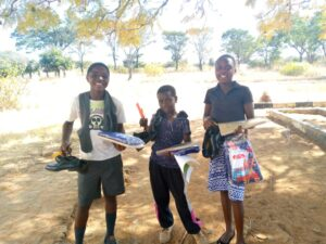 Picture of three school children holding their new uniform and school supplies